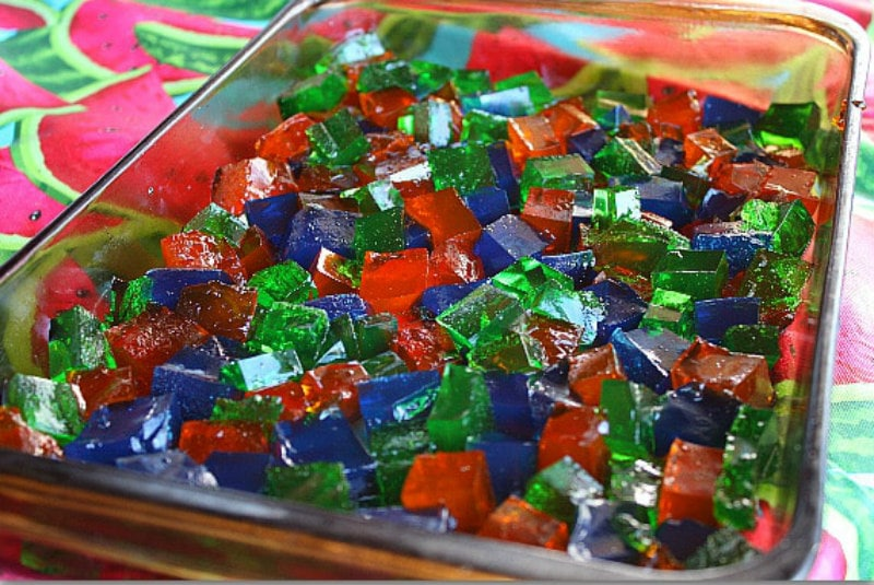 chopped up pieces of different colors of jello in a pyrex pan