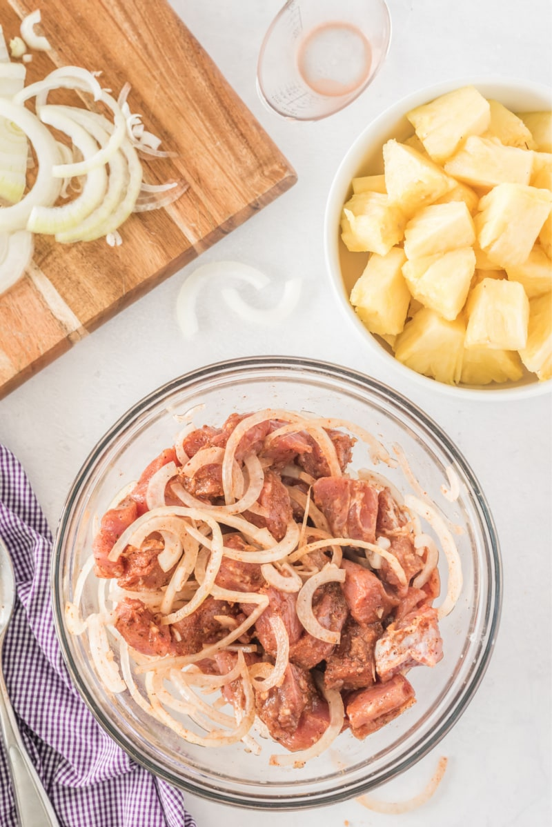 marinated pork in a bowl with pineapple in another bowl