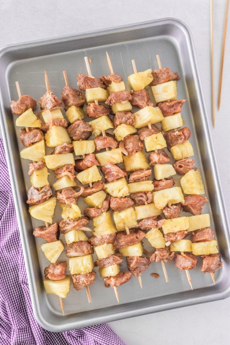 pork and pineapple kebabs on baking sheet