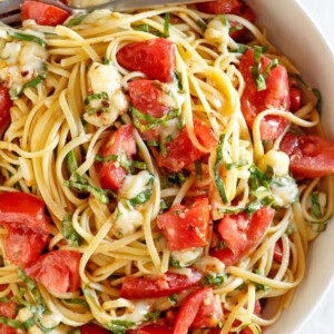 overhead shot of white bowl of linguine with tomatoes basil and brie with a fork