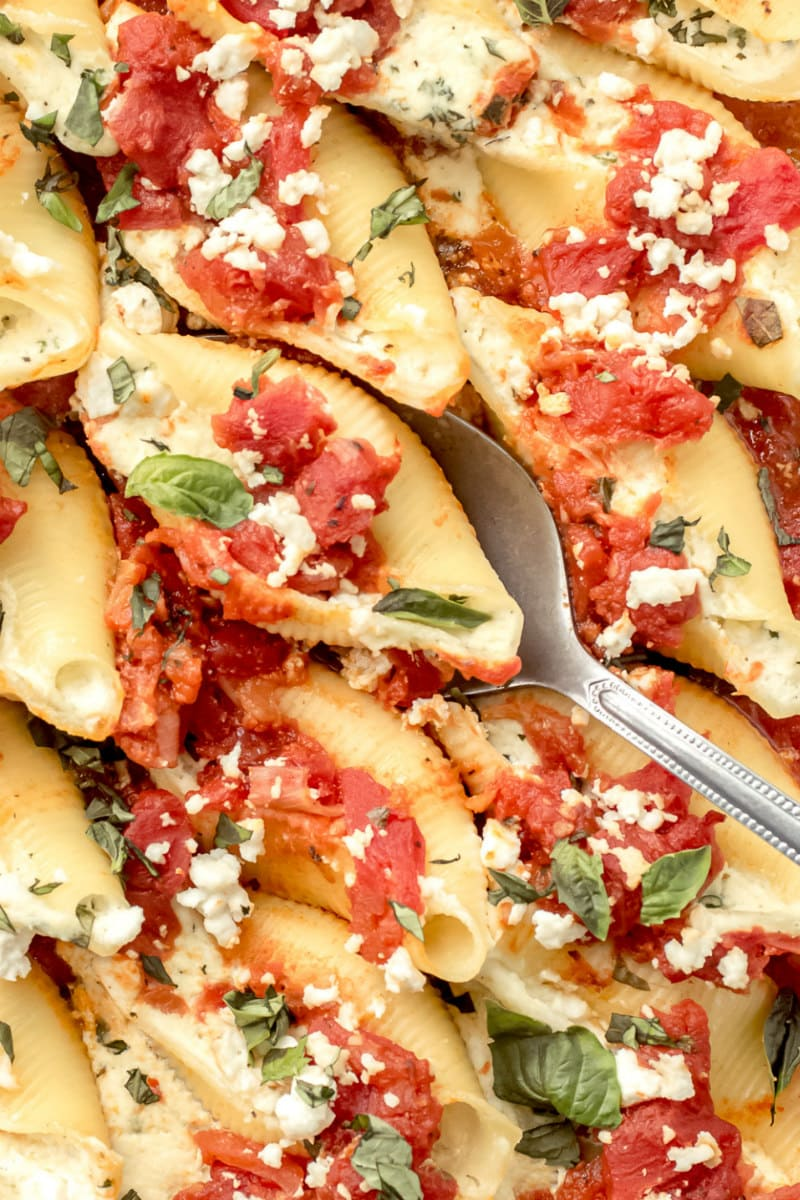 spooning out pasta shells filled with feta and herbs