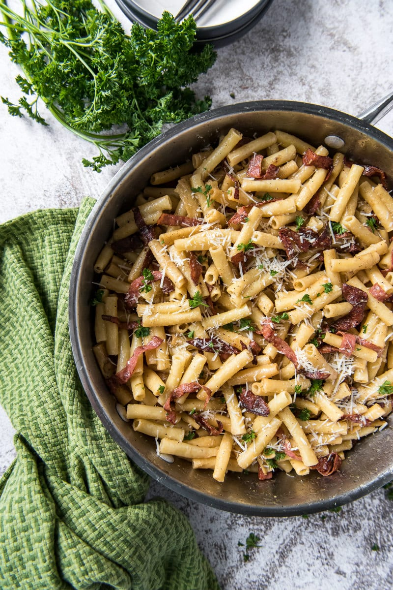 skillet filled with ziti carbonara sitting on a green cloth napkin with fresh parsley on the side
