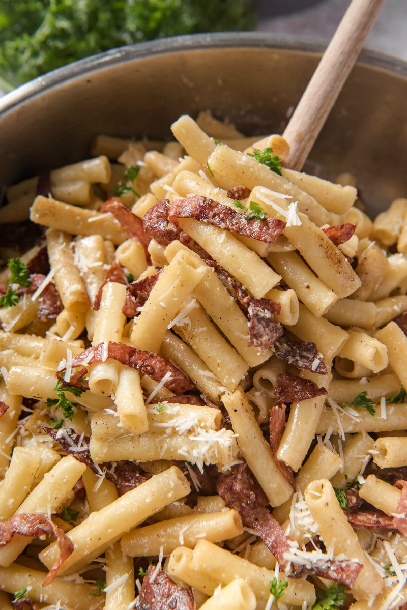 dishing out serving of ziti carbonara from a skillet