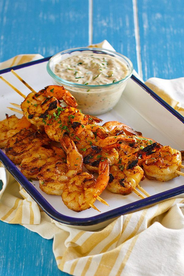 Barbecued shrimp on skewers with a bowl of remoulade sauce served on the side. Set on a white platter with a blue rim. Yellow striped napkin underneath. All set on a blue board background.