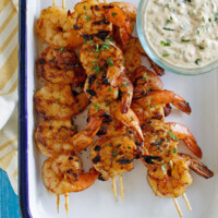 Barbecued shrimp on skewers with a bowl of remoulade sauce served on the side. Set on a white platter with a blue rim. Yellow striped napkin underneath