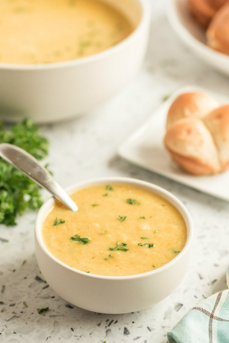 butternut squash soup in white bowl with spoon