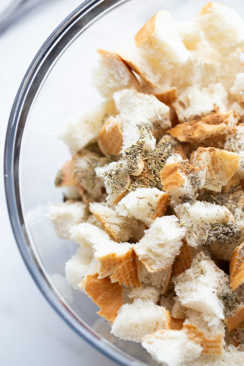 bread cubes with seasoning in glass bowl