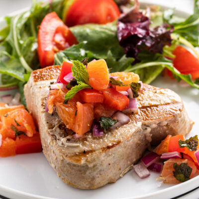 grilled tuna with citrus salsa on a plate with salad