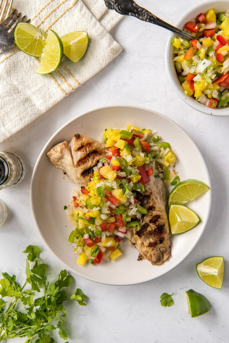 overhead shot of red snapper with pineapple salsa on a white plate