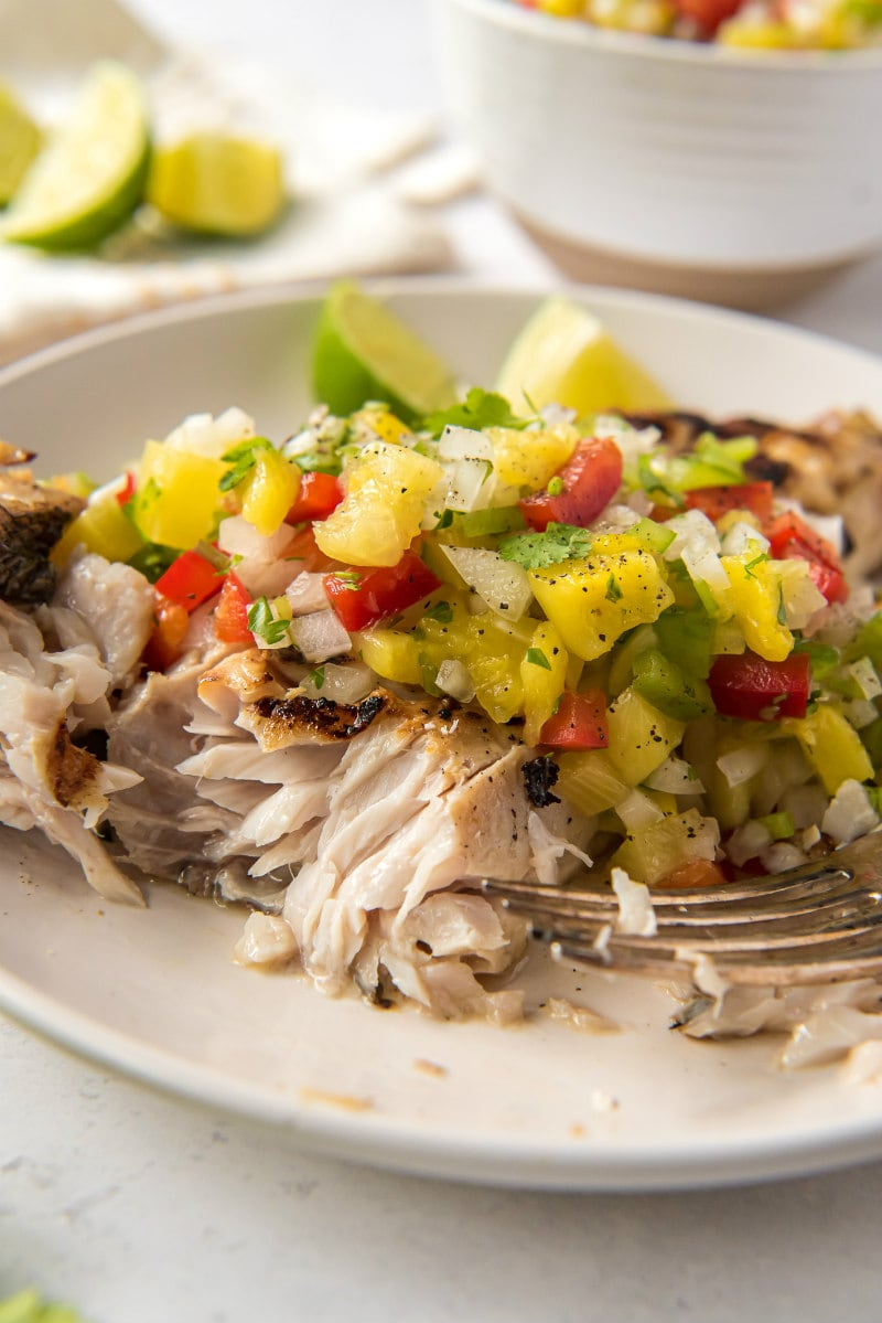 red snapper flaked open with a fork and served with pineapple salsa on a white plate