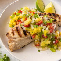 red snapper with pineapple salsa on a white plate