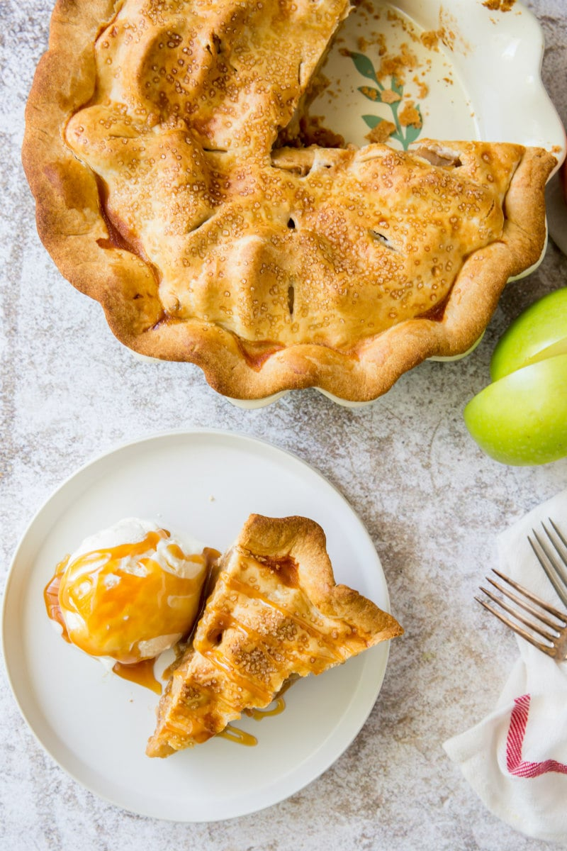 apple pie with slice cut out plated on white plate with ice cream