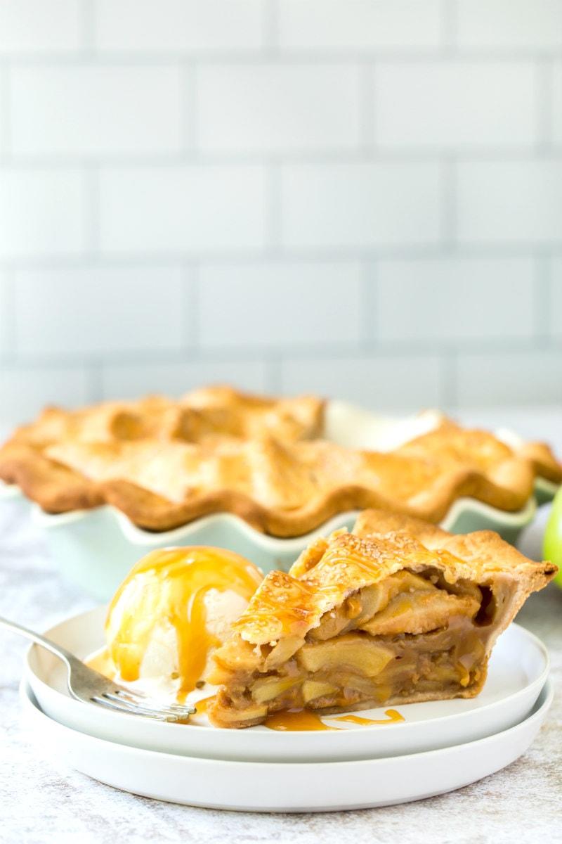 slice of dulce de leche apple pie on white plate with ice cream