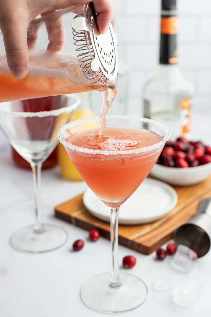 pouring cranberry margarita into glass