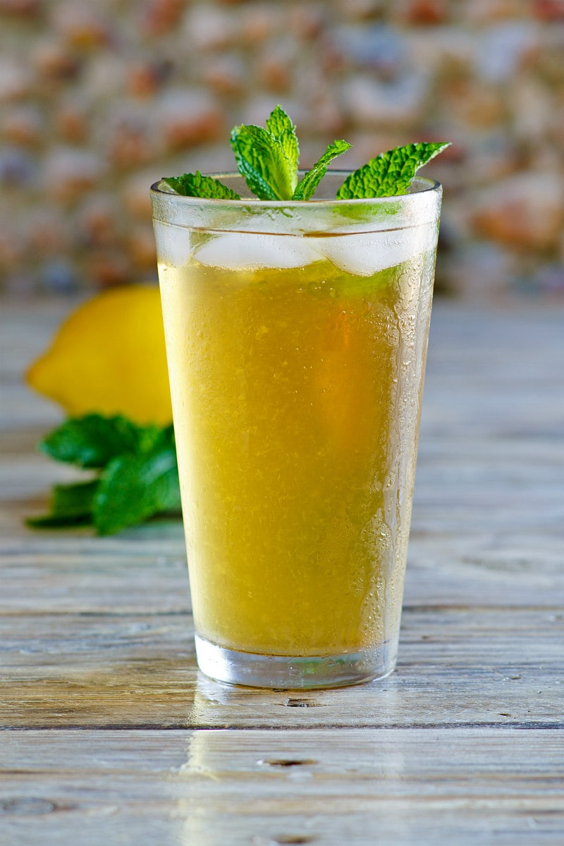 Sweet Summer Iced Tea garnished with fresh mint with a fresh lemon in the background
