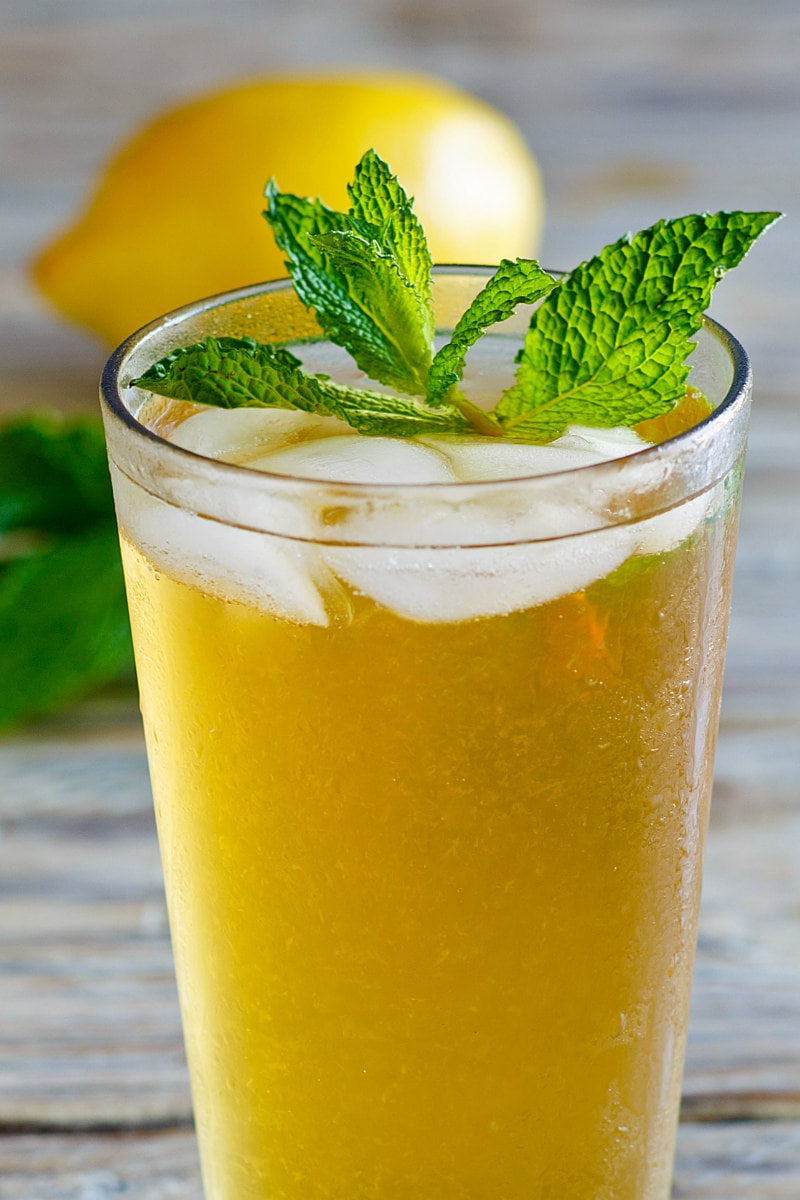 a glass of sweet summer iced tea garnished with fresh mint with a lemon in the background