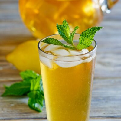Sweet Summer Iced Tea garnished with mint with a pitcher of iced tea in the background