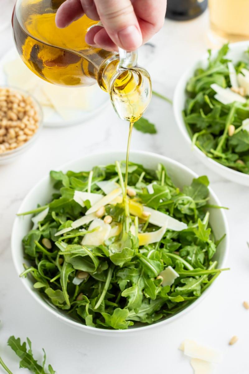 pouring oil onto insalata romantica