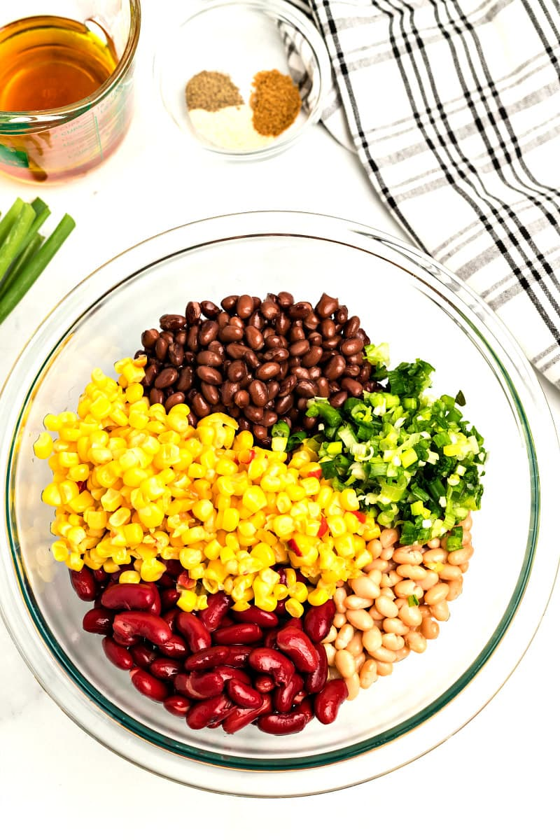 ingredients for red white and black bean salad in a glass bowl with a plaid napkin and green onions garnish