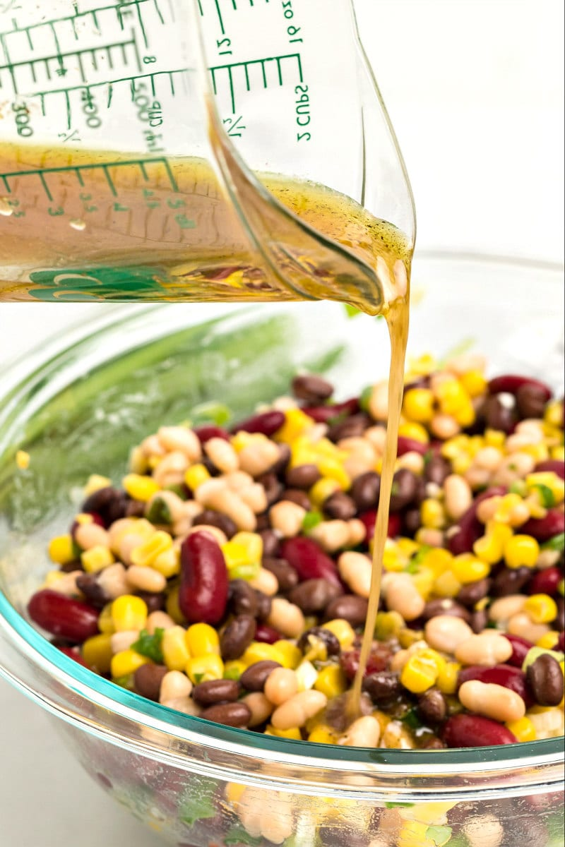 pouring dressing onto red white and black bean salad in a glass bowl