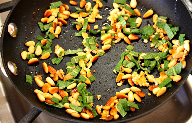 sage and pine nuts in a skillet