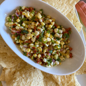 corn and sundried tomato salsa in a white bowl surrounded by tortilla chips