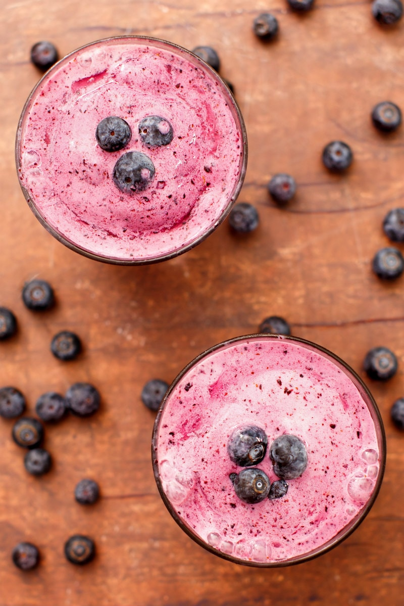 overhead shot of two blueberry lemon smoothies garnished with fresh blueberries and more fresh blueberries scattered around