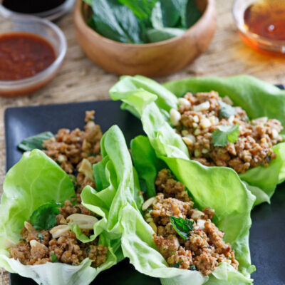 asian lettuce wraps on a black plate with bowls of ingredients in the background