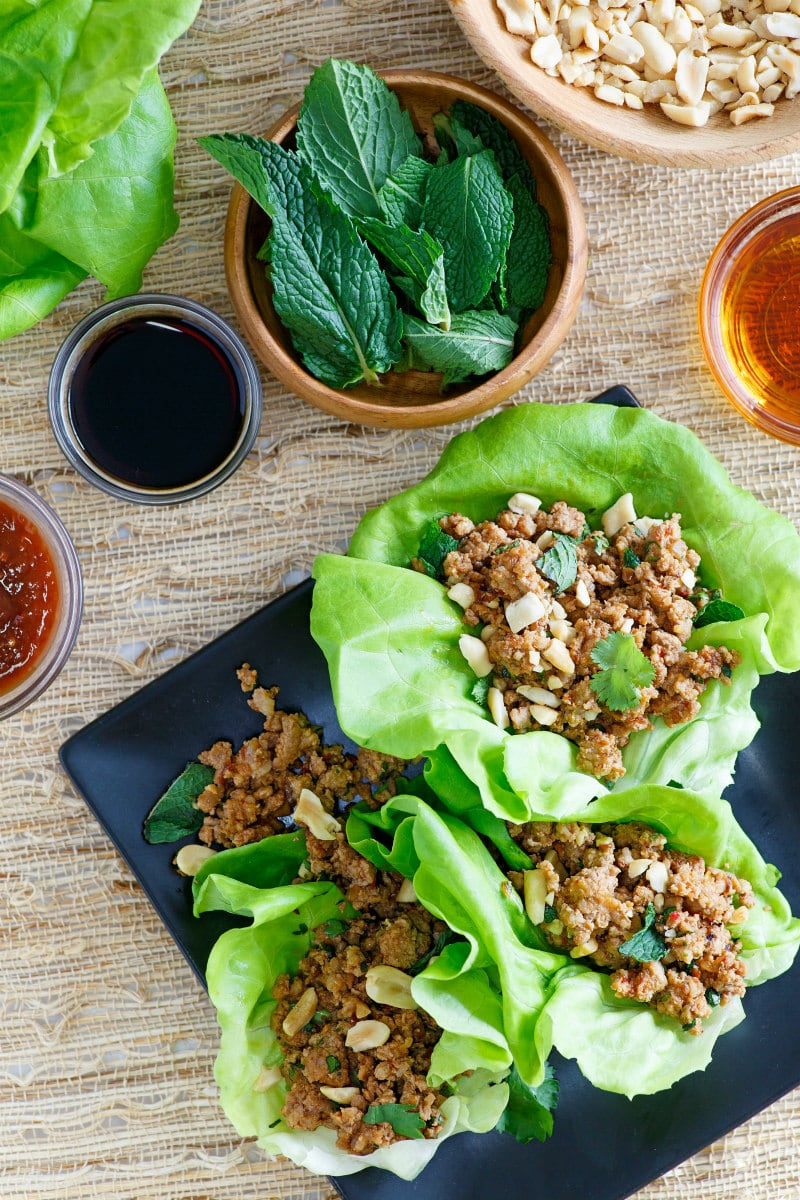 overhead shot of asian lettuce wraps on a black plate with bowls of the prep ingredients displayed