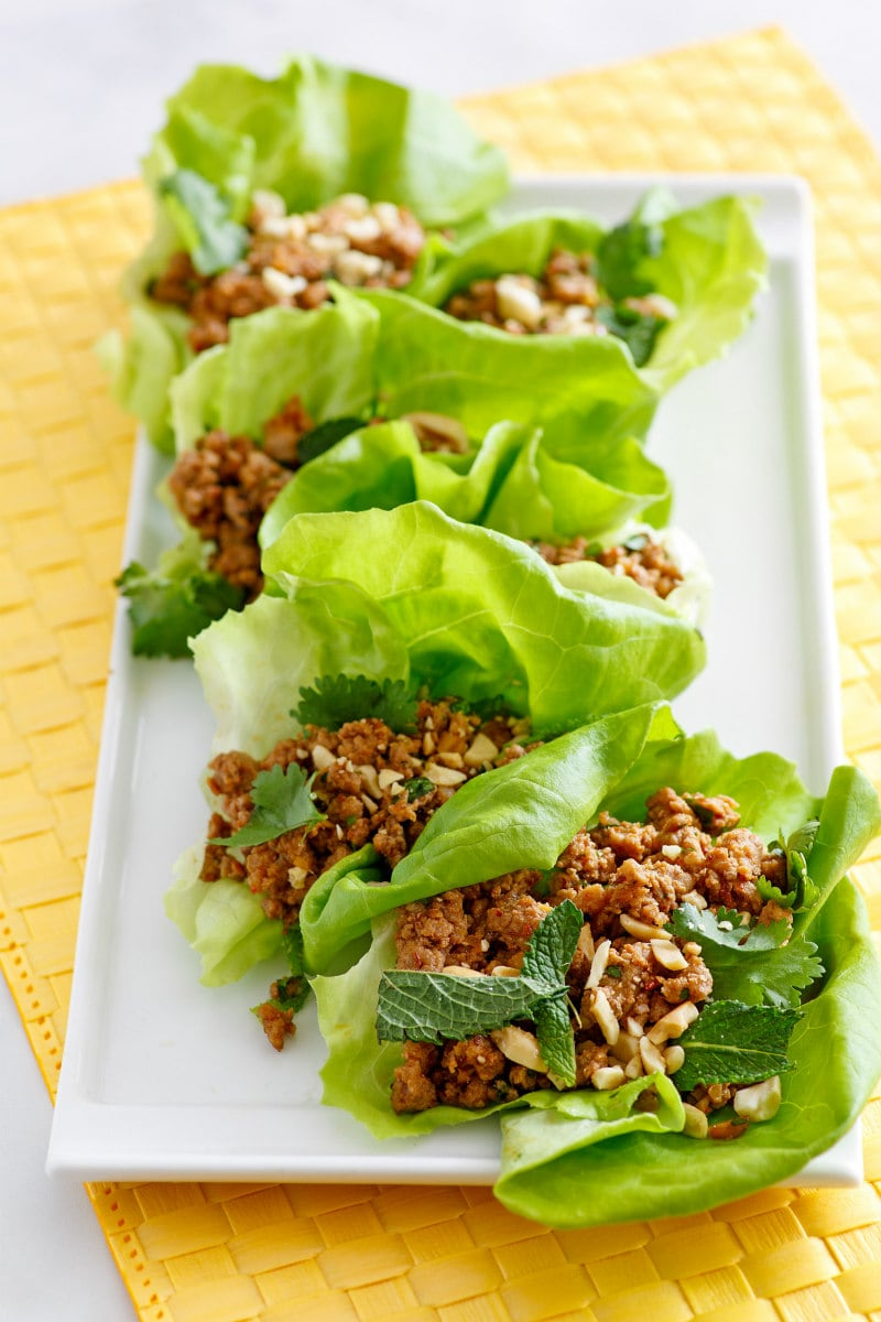asian lettuce wraps on a white plate set on a yellow napkin