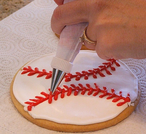 How to Make Baseball Cookies : adding red stitching with royal icing