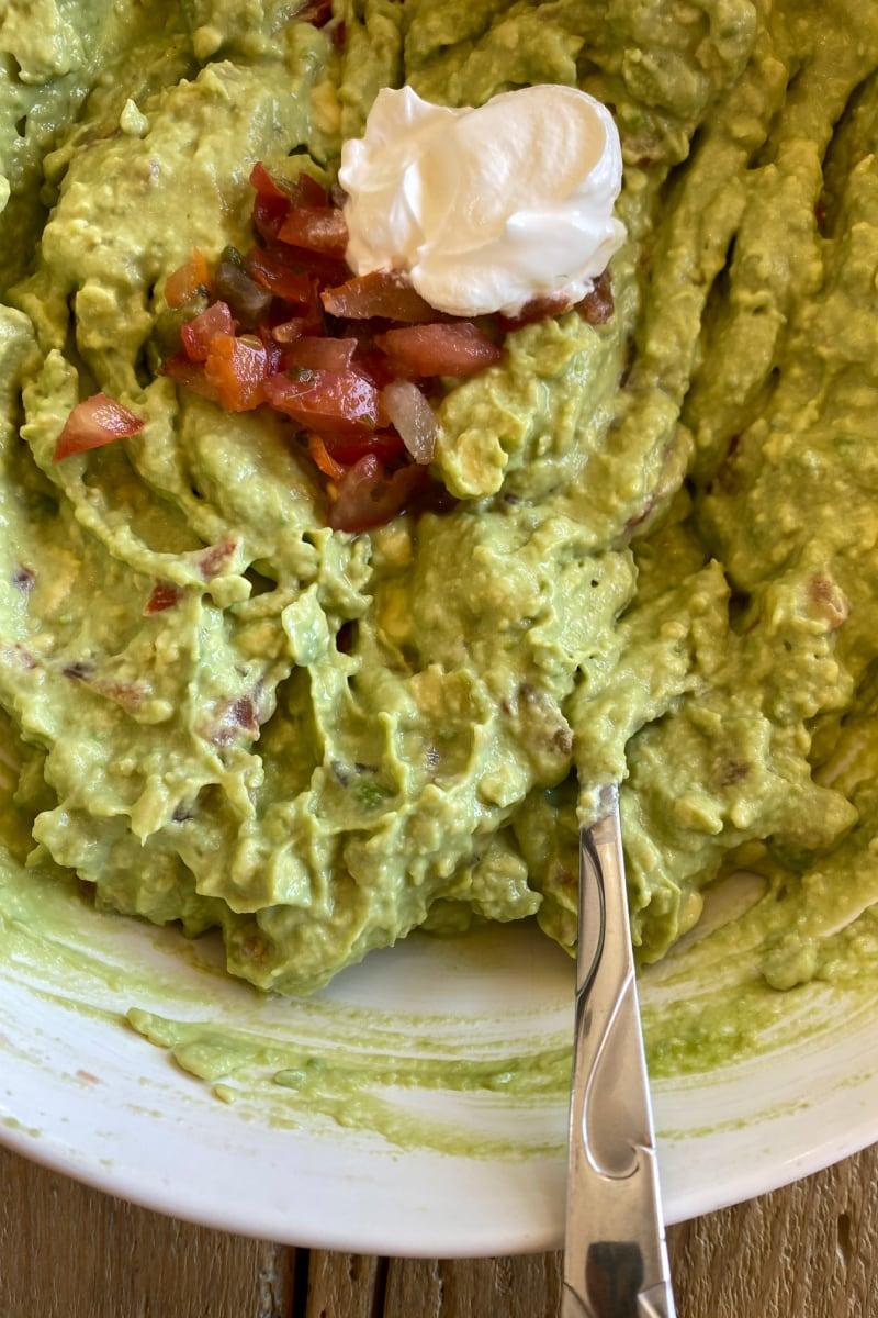 making guacamole in white bowl