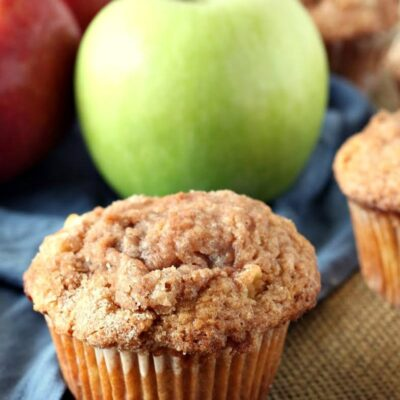 apple cinnamon muffin displayed in front of green and red apples with a blue cloth napkin