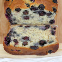 loaf of banana blueberry bread sliced open to see the inside. set on a cutting board
