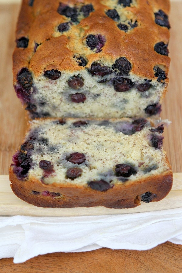 Banana Blueberry Bread loaf on a cutting board, cut open to see the inside