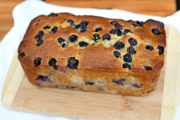 loaf of Banana Blueberry Bread sitting on a cutting board