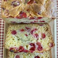cranberry orange bread sliced on cutting board