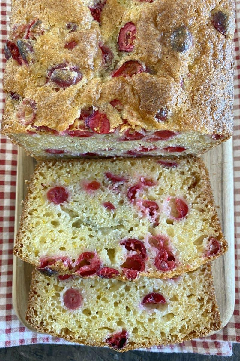 cranberry orange bread sliced on cutting board