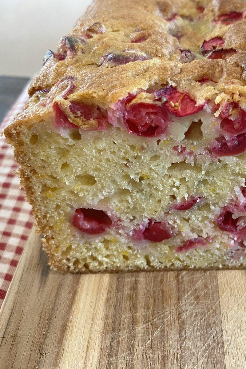 sliced open cranberry orange bread on wood board