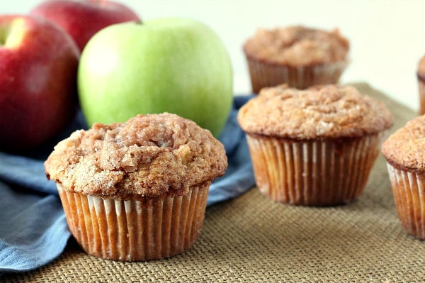 apple cinnamon muffins displayed in front of green and red apples with a blue cloth napkin