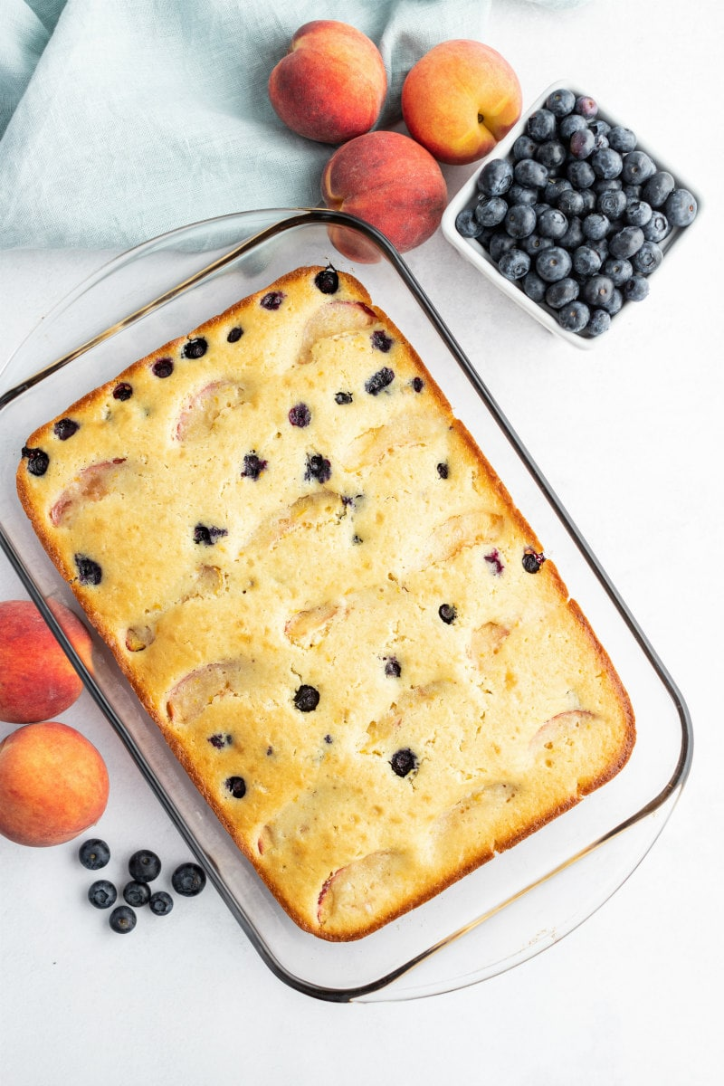 overhead shot of peach and blueberry coffee cake in a pyrex pan with fresh peaches and blueberries scattered in the background