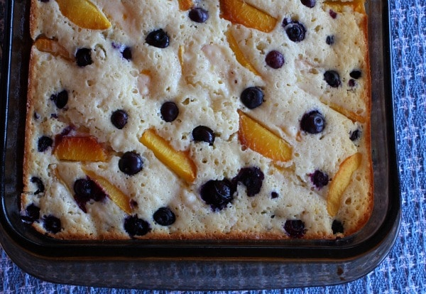 Overhead shot of half of the pan of peach and blueberry coffee cake