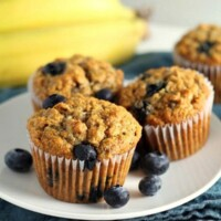 whole wheat banana blueberry muffins (3) on a white plate with fresh blueberries scattered about and bananas in the background
