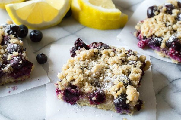 Blueberry Lemon Crumb Bars sitting on parchment paper with fresh cut lemons in the background