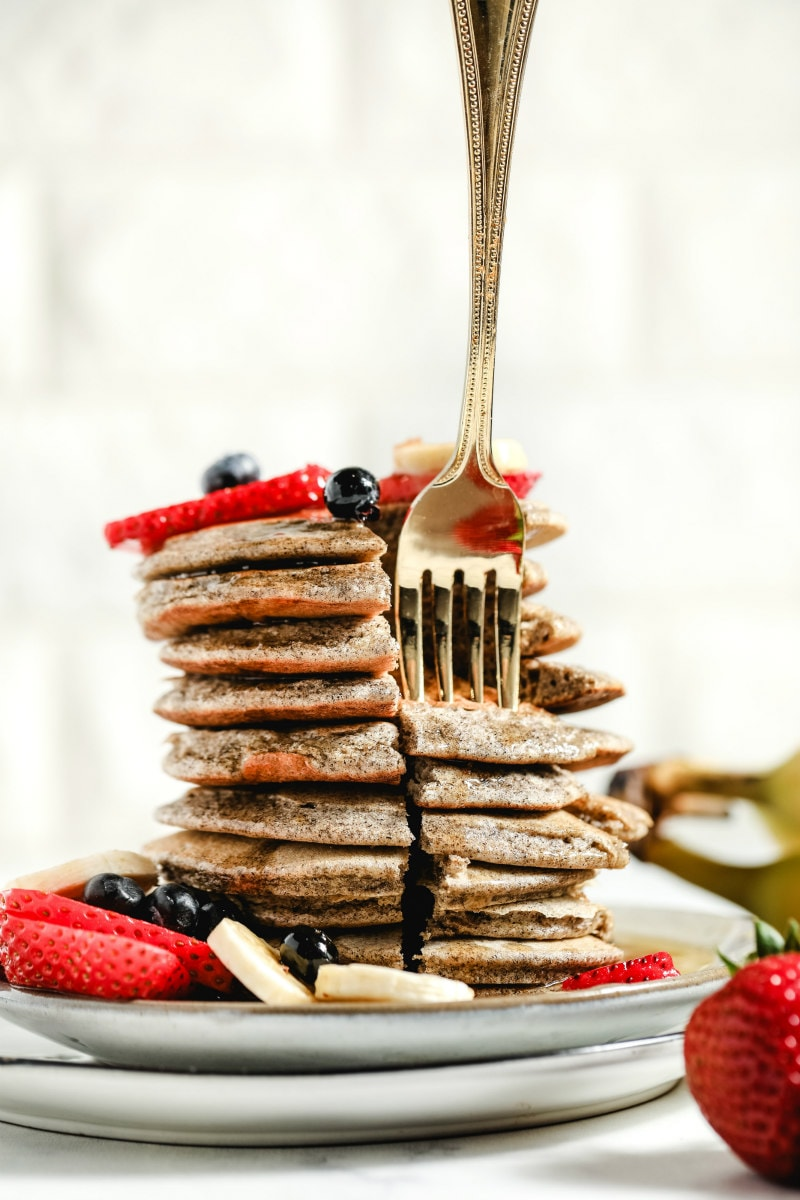 forkful of buckwheat pancakes arranged in a tall stack on a white plate, garnished with fresh berries and bananas