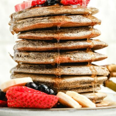 stack of buckwheat pancakes on a white plate with syrup drizzling down the sides, garnished with fresh berries and bananas