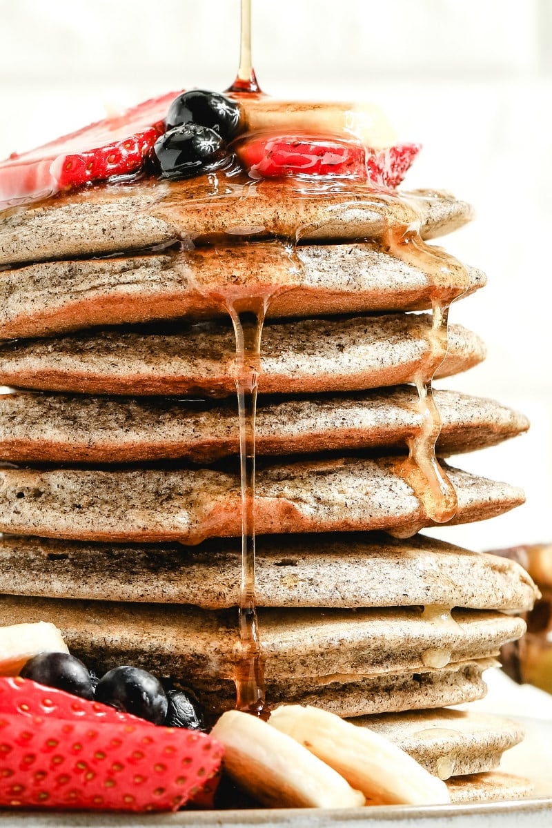 syrup falling down the sides of a stack of buckwheat pancakes garnished with fresh berries