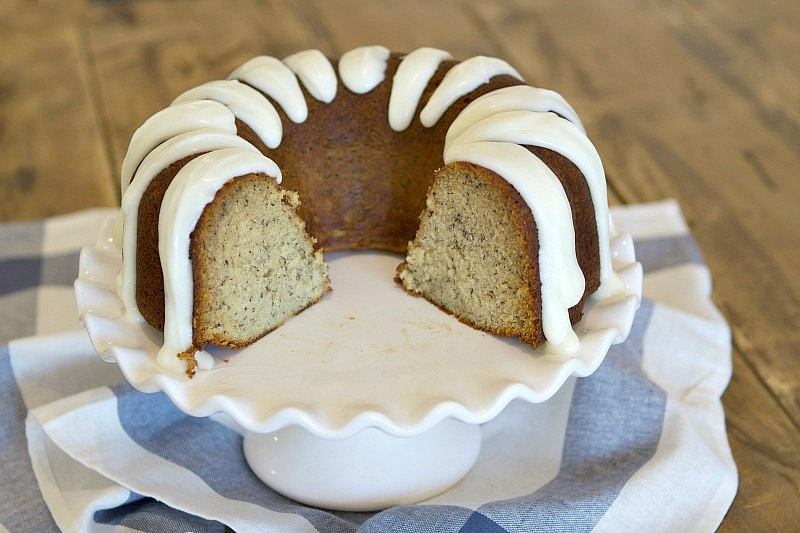 banana bundt cake with cream cheese frosting with a chunk taken out of it displayed on a white cake platter on top of a blue and white striped napkin
