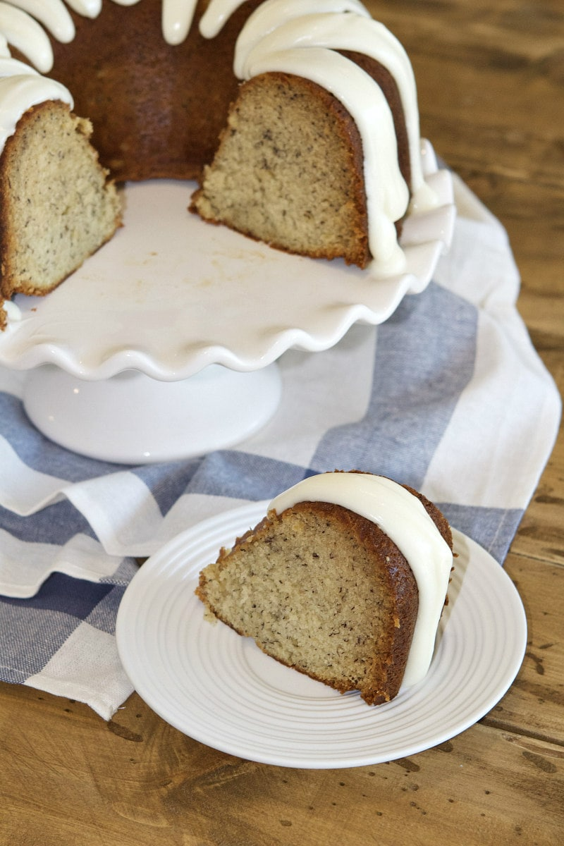 banana bundt cake on a white serving platter with a slice of banana bundt cake on a white plate in front of it. Set on a blue and white striped napkin on a wooden table