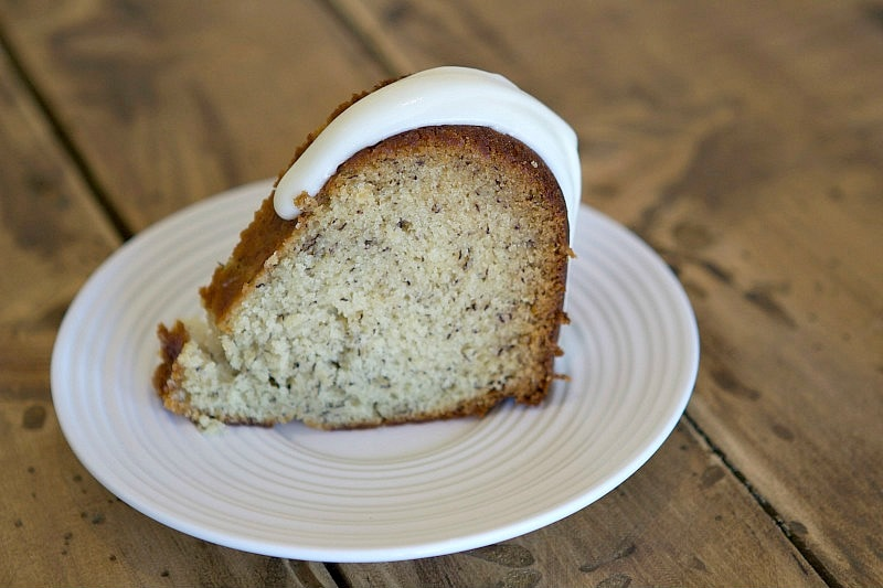 slice of banana bundt cake on a white plate set on a wood background